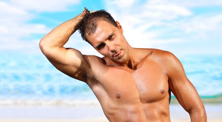pectoral muscle: sexy caucasian fit man posing in a beach  Stock Photo