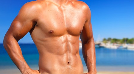 sin camisa: sexy caucásico encajar a hombre posando en una playa  Foto de archivo