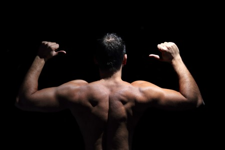 The muscular male back on black background.