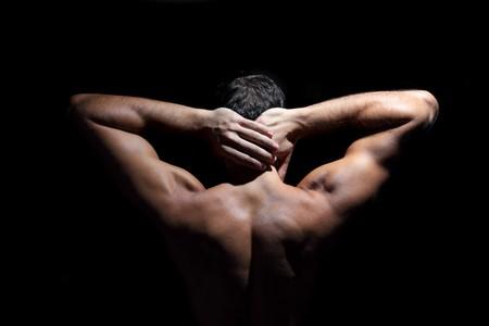 Die muscular Male zurück auf schwarzem Hintergrund.