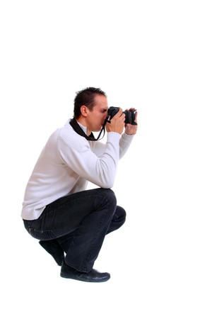 crouching: Portrait of male photographer with camera isolated on white background