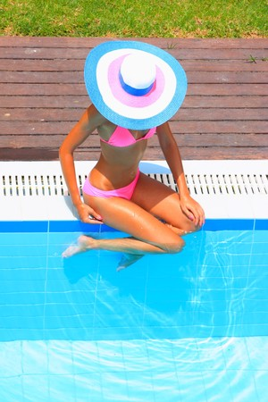 Woman in a pool hat relaxing in a blue pool  Banque d'images