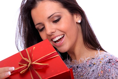 christma: winter portrait of a beautiful young smiling woman with a gift
