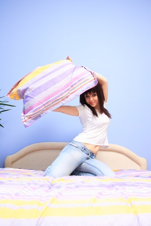 Woman having pillow fight in bed photo