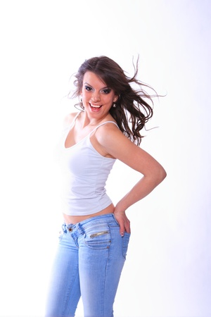 chearful: smiling young woman in jeans and t shirt, studioshot over neutral background Stock Photo