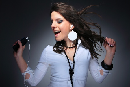 enjoy space: Beautiful Girl listening music with her cell phone over gray background