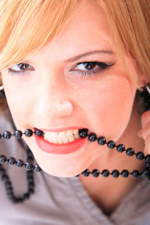 woman open mouth: Woman open mouth and teeth biting on faux pearls