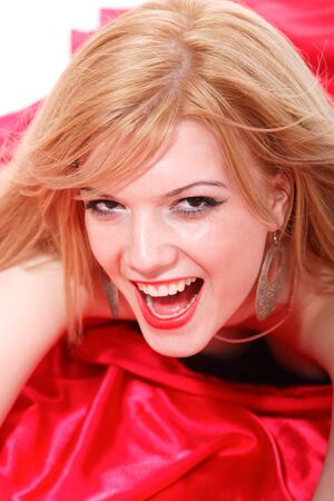 bedsheets: A beautiful young blonde woman in a bed of red silk sheets