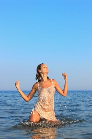 Beautiful young woman in the sea spashing water photo