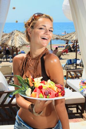 Young smiling woman with fruits salad by the sea photo