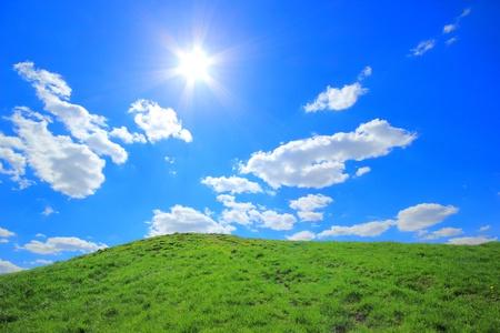 Green grass hills under midday sun in blue sky.