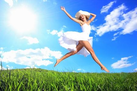 Frau Freude springen, auf eine Gras-Hügel