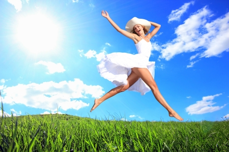 Woman  Jumping for Joy on a Grass Hill photo