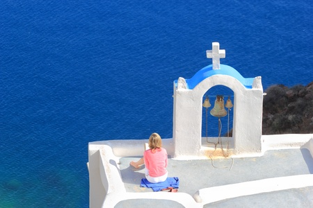 Young woman reading a book and enjoying the view of Santorini island Greece Stock Photo - 9662456