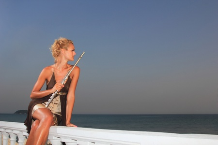Beautiful young sexy fashion model with flute by the sea at sunset in Greece photo