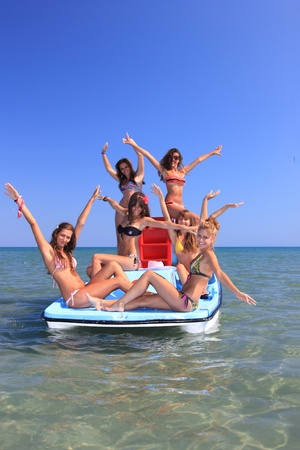 yellow boats: Group of six beautiful young women on a pedalo boat