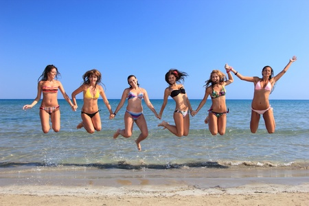 swimsuit: Group of Six Attractive girl jumping on the beach in Greece