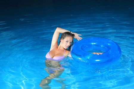 Attractive girl posing in swimming pool at night photo