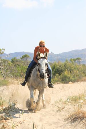 horse blonde: Young female rider on the beach