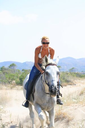 horse blonde: Young female riding her horse by the sea in Greece Stock Photo