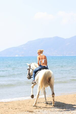 Young female riding her horse in the sea in Greece photo