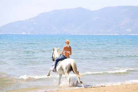 Young female riding her horse in the sea in Greece Stock Photo - 10913848