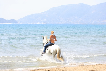 Young female riding her horse in the sea in Greece Banque d'images