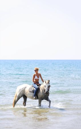 Young female riding her horse in the sea in Greece Stock Photo