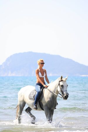 horse blonde: Young female riding her horse in the sea in Greece Stock Photo
