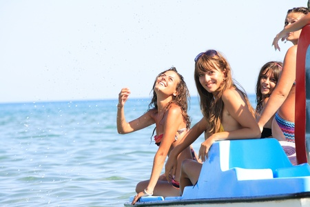 Group of four beautiful young women on a pedalo boat Stock Photo
