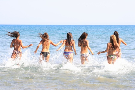 Group of Six Attractive girls running in the sea in Greece