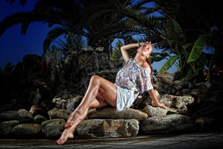 fontaine: Beautiful young woman sitting on the rocks Stock Photo