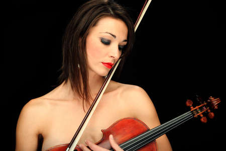 Woman holding a violin over a black background. photo