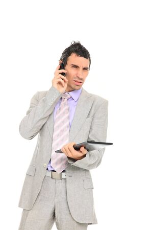 young business man standing using a tablet and talking on the phone isolated on white background photo