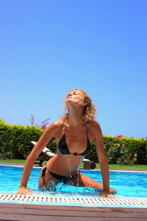 Beautiful young woman at the swimming pool in her private villa photo
