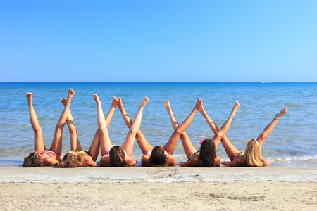 Group of six beautiful young girls laying on the beach legs up photo
