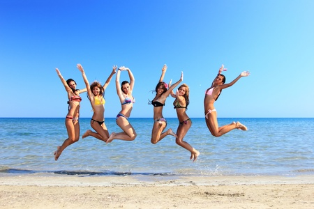 Gruppe der Sechs Attraktive Mädchen springt am Strand in Griechenland