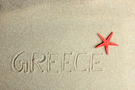 Greece written in the sand and Red starfish on the beach photo
