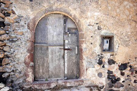 A very worn and battered old blue door situated on the Greek isle of Santorini. Stock Photo - 13680377