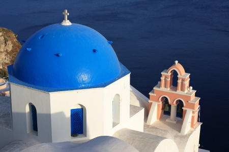 Traditional Greek white church arch with cross and bells in village Oia of Cyclades Island Santorini Greece photo