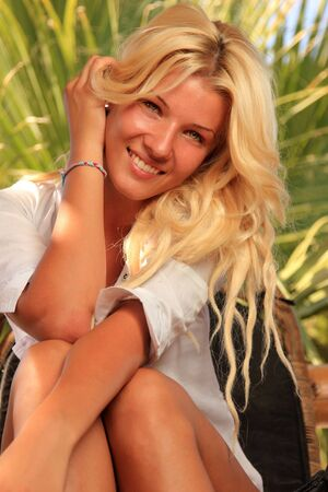 Young woman wearing a white shirt at tropical resort Stock Photo - 15051756