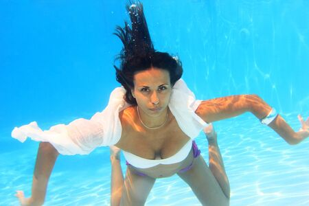 Woman wearing a white shirt swimming underwater in the pool