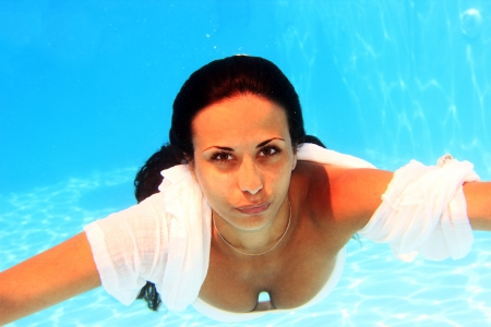 underwater woman: Woman wearing a white shirt swimming underwater in the pool