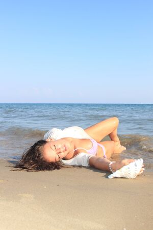 fira: Young woman on the beach enjoying the summertime Stock Photo