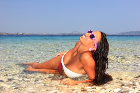 Young woman enjoying the summer time on the beach photo