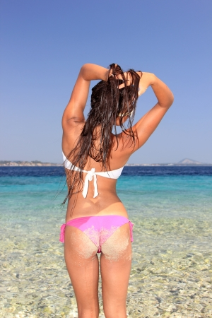 Back view of a young woman enjoying the summer time on the beach photo