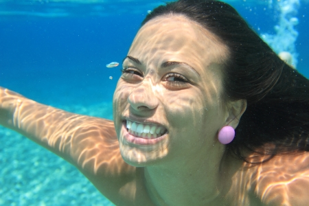 Woman swimming underwater in the sea smiling. Young female swimmer at holiday resort. Фото со стока