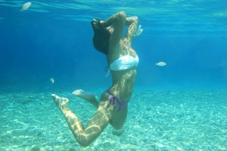 Woman swimming underwater in the sea smiling. Young female swimmer at holiday resort. photo