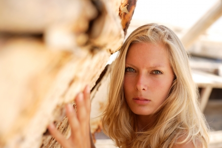 portrait of sexy blond woman posing in from of shipwreck Stock Photo