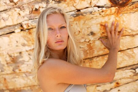 portrait of sexy blond woman posing in from of shipwreck photo